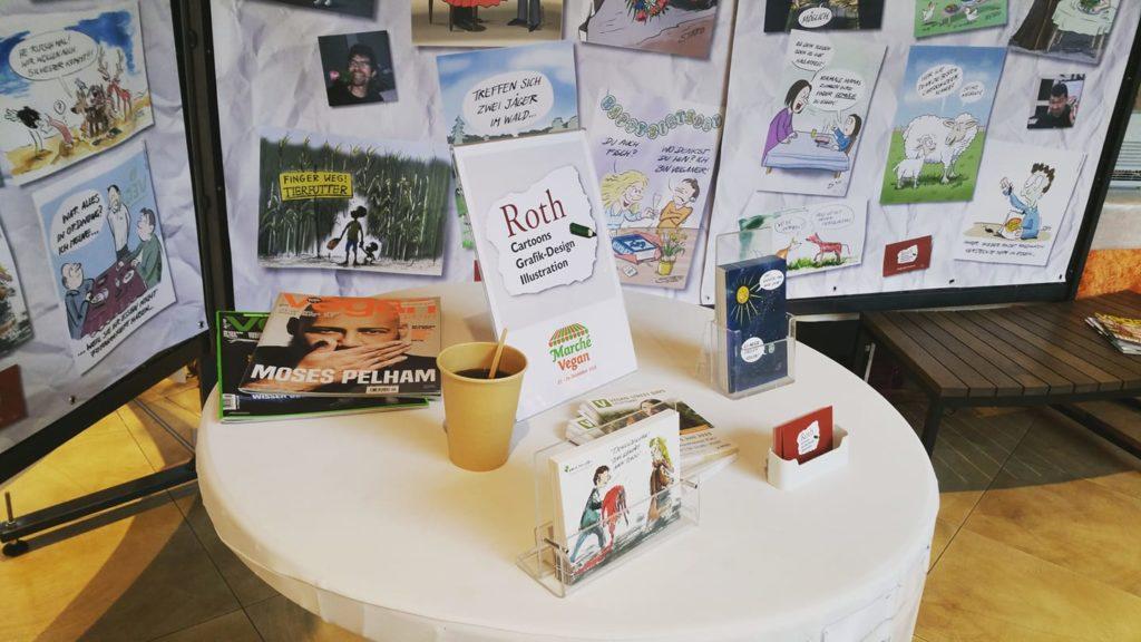 Stehtisch mit Postkarten und Visitenkarten von Cartoonist Stefan roth - roth-cartoons in Ulm im Blautalcenter beim marche vegan 2018